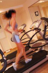 Běžkyně na běžícím páse v posilovně