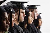 Studenti v řadě s čepicemi na hlavě